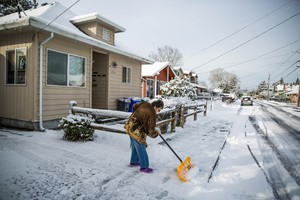 Carolyn McMahon shovels her driveway in Southeast Portland, Wednesday, Feb. 21, 2018.