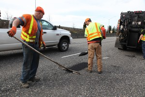 An ODOT maintenance crew fills potholes on Highway 26.