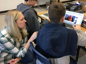 8th grade U.S. History teacher, Shanna Davis, helps a student with his project.