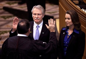 Oregon Gov. John Kitzhaber, center, is joined by his fiancee, Cylvia Hayes, as he is sworn in for an unprecedented fourth term by Senior Judge Paul J. De Muniz in Salem, Ore.