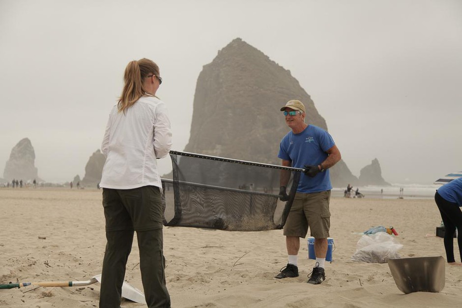 Valerie Schockelt (left) and Marc Ward use a microplastics filtration device to filter sand on Cannon Beach with iconic Haystack Rock in the background.