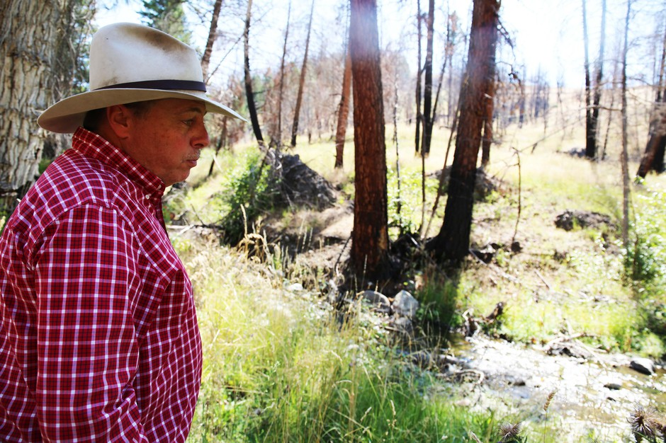 Gordon Larsonwatches a stream go by on his Grant County ranch.