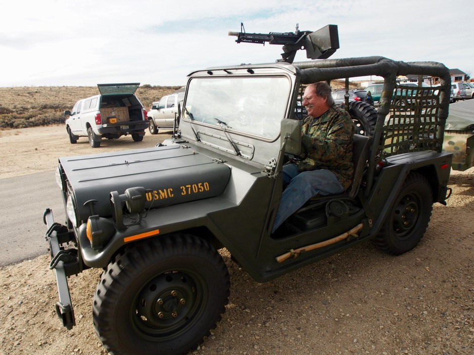 Roy Cagnacci drives his Vietnam-era Ford Mutt mounted with a belt-fed machine gun at the Idaho Automatic Weapons Collectors' Association annual Pumpkin Shoot. The group is part of a subculture of gun owners who collect heavily-regulated machine guns.
