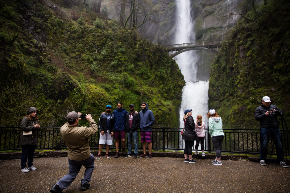 Tourists take pictures next to Multnomah Falls, April 13, 2018.