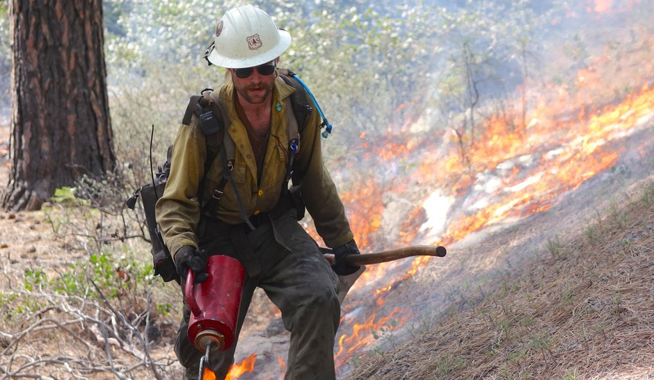 A member of the Wolf Creek Hotshots uses a drip torch to ignite the forest floor during a prescribed burn near Sisters, Oregon.