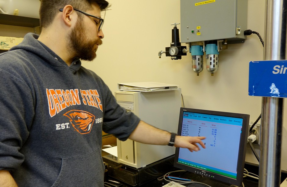OSU researcher Byrne Miyamoto monitors how much weight a piece of Western Juniper can hold.