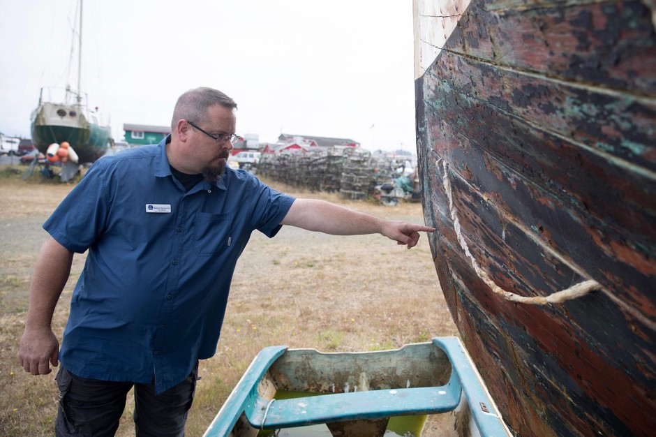 """Troy Wood, derelict vessel removal program manager for the stateDepartment of Natural Resources, points out damage on an aging wooden-hulled vessel that could be a """"future customer"""" of a boat recycling center in Ilwaco, Washington."""