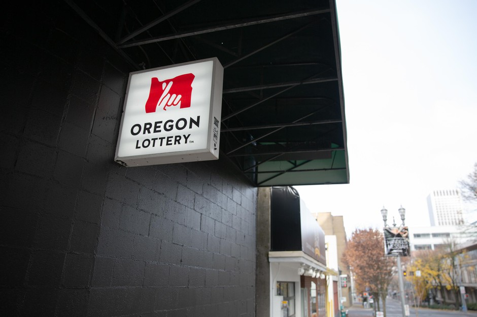 An Oregon Lottery sign hangs outside the Cheerful Tortoise bar in Portland, Ore., Nov. 24, 2018. The lottery has released a new sports betting smartphone app called Scoreboard.