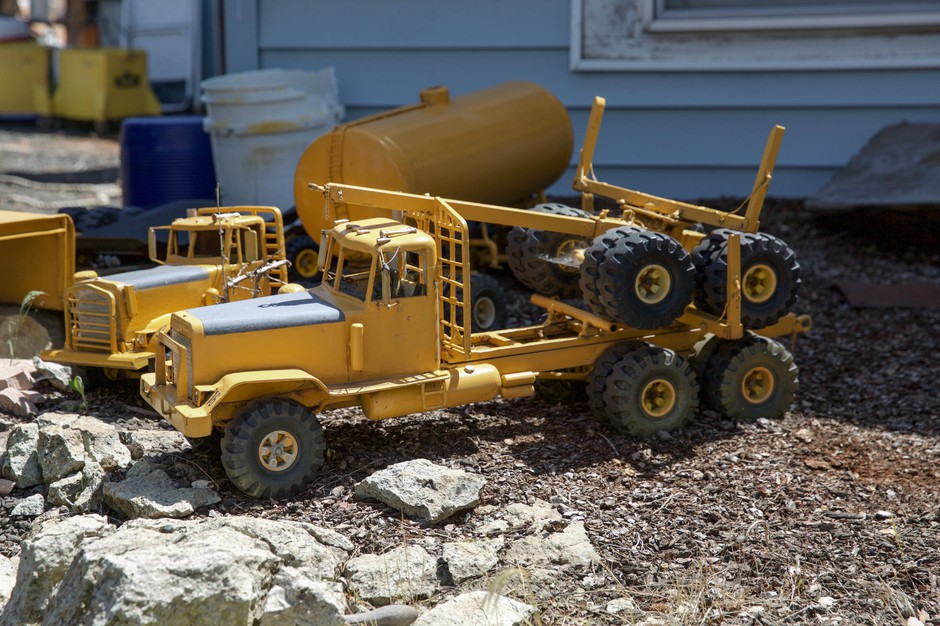 Model trucks sit in Otis Cody's front yard in Fossil, Ore., Tuesday, June 4, 2019. Cody handmakes the trucks himself down to the tiny steering wheels and moving parts.