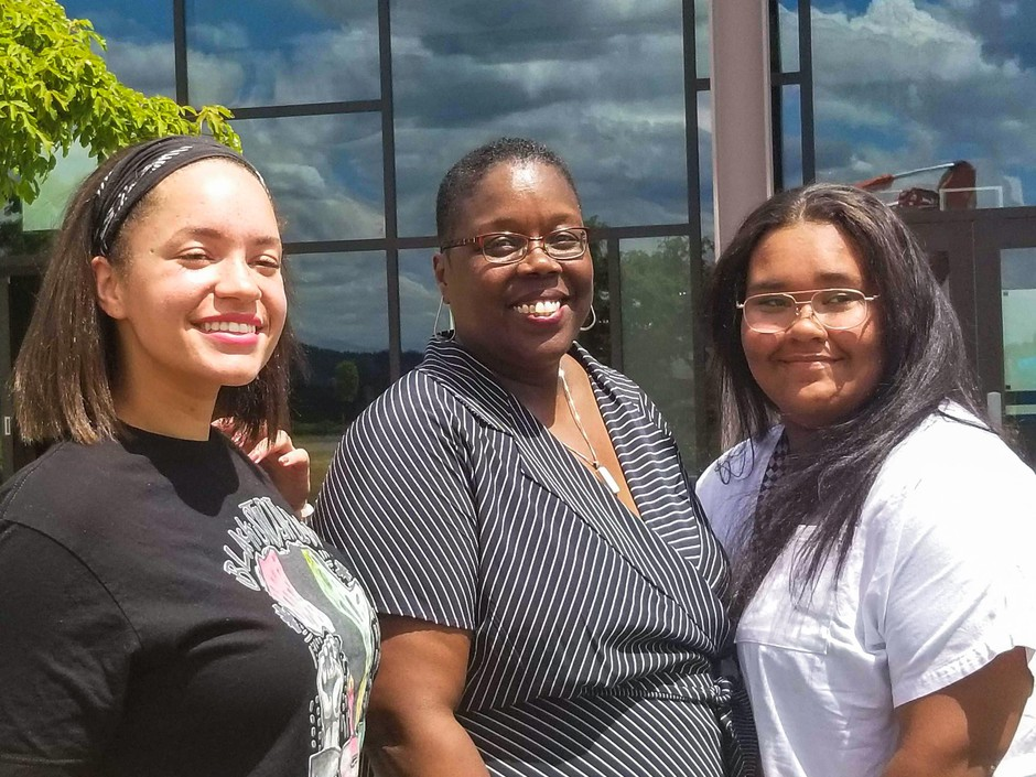 Adrienne C. Nelson High School is the name of North Clackamas school district's newest high school. Justice Nelson (center) stands at the site with members of Clackamas High School's Black Student Union who advocated for the school's name. Brianna Gibson, Vice President (left) and Kaylee Hicks, President (right).