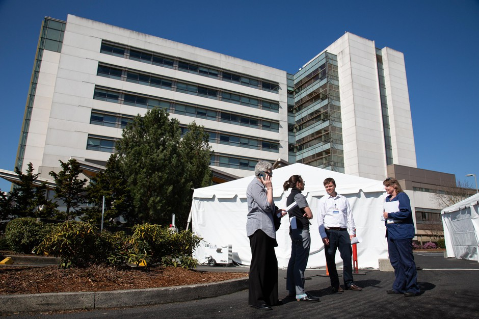 PeaceHealth Southwest staff talk in front of newly erected triage tents outside the emergency room in Vancouver, Wash. Hospitals are taking steps to prepare for a surge in patients from the novel coronavirus.