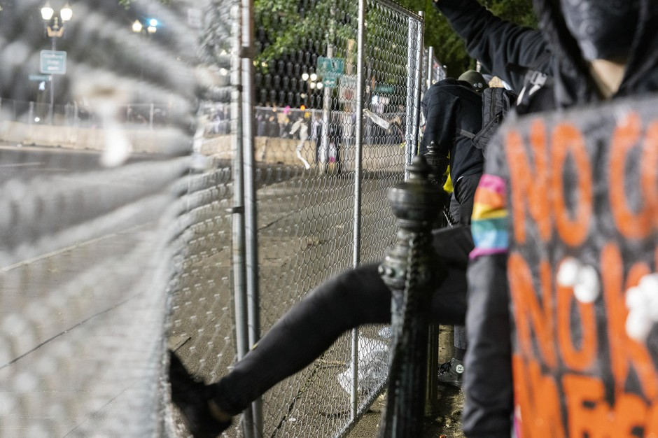 A person kicks the fence surrounding the Multnomah County Justice Center during protests over police brutality in Portland, Ore., June 5, 2020.