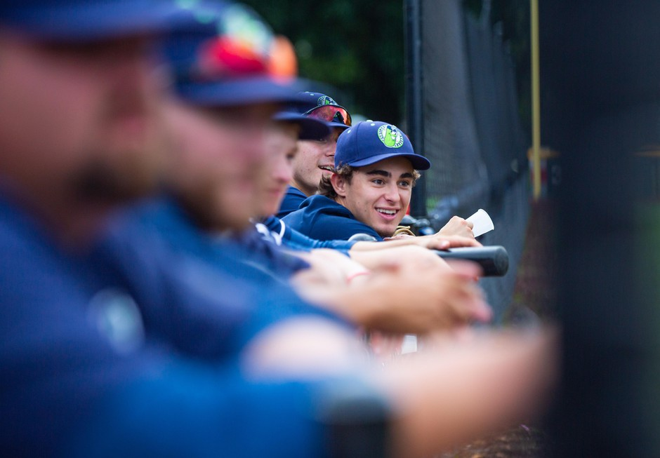 Pickles players lean against the dugout.