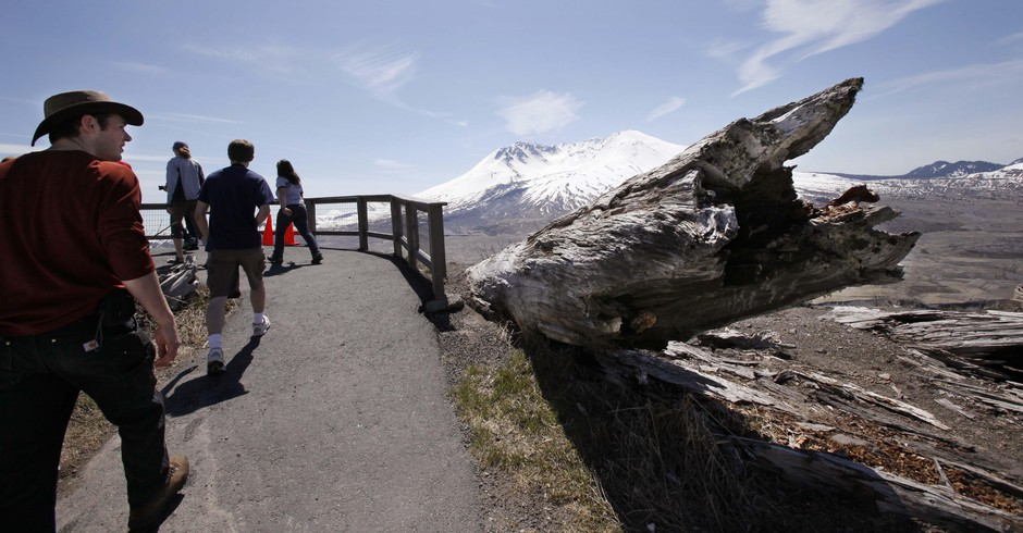 Visitors walk past a tree still pointed away from the blast where it was knocked down nearly three decades earlier at what is now the Johnston Ridge Observatory at Mount St. Helens National Volcanic Monument, Friday, May 14, 2010, near Toutle, Wash.