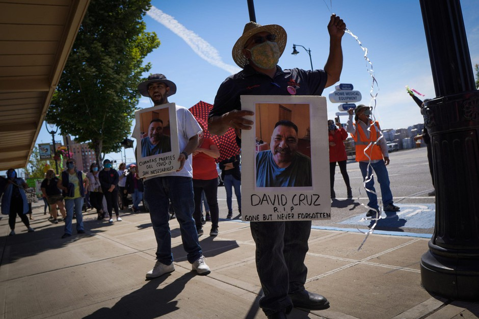 Farmworkers in Yakima, Washington's fruit packing industry walked off production lines in May and went on strike, demanding more protections against the coronavirus pandemic. Emmanuel Anguiano-Mendoza (left) and Agustin López hold posters featuring David Cruz, a worker who died on May 30.