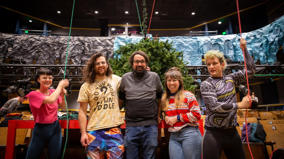 "Stage hands raise the Christmas tree during a ""Batman Returns Returns"" rehearsal at Revolution Hall. Producers Neil Fridd (center left), Zack Traeger (center), and writer/director Megan Tabaque (center right)."