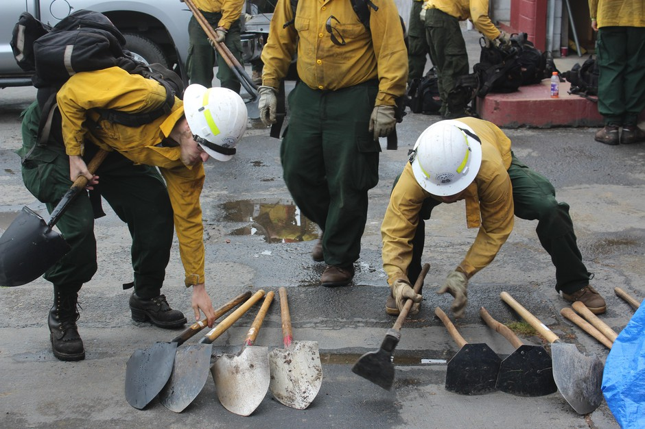 Firefighters with the private contracting outfit Inbound LLC stack shovels and other hand tools at the company's headquarters in Oakridge, Oregon.