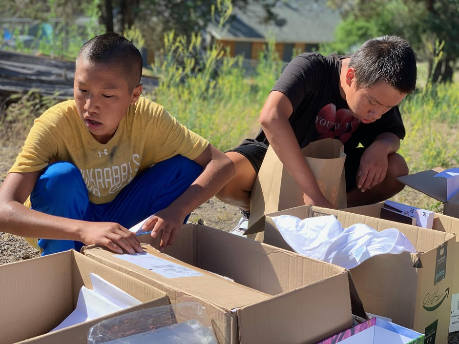 Dean (left) and Marcus (right) Muldrow — 14-year-old ninth graders at Madras High School and Warm Springs residents — sift through boxes of free T-shirts, given out by Jefferson County School District staff at the end of the school year, Thursday, June 4, 2020.