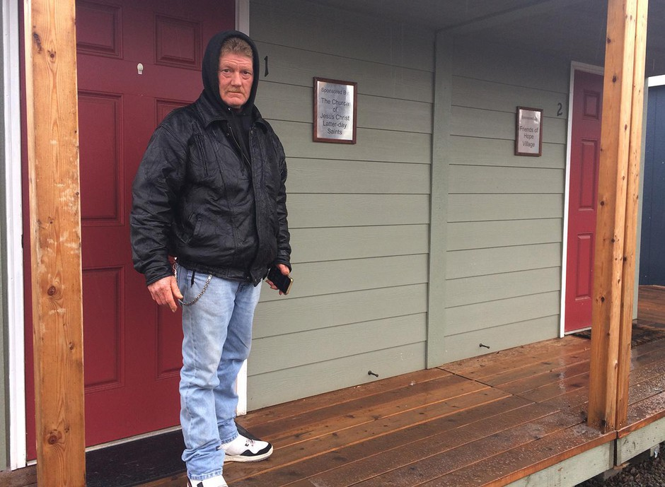 Buckshot Cunningham stands in front of a small cottage at Hope Village, a tiny house shelter run by the nonprofit Rogue Retreat in Medford, Ore.