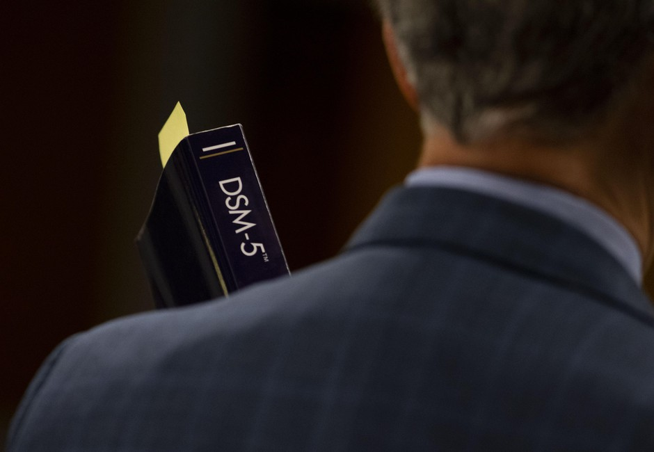 Prosecutor Don Rees holds a copy of the Diagnostic and Statistical Manual of Mental Disorders, or DSM, at the Multnomah County Courthouse in Portland, Ore., Feb. 12, 2020.