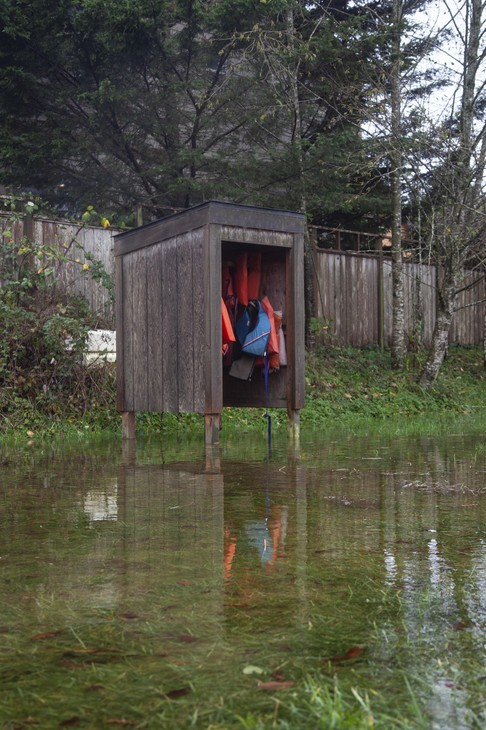 A cabinet of life jackets, free for visitors to borrow, is surrounded by water during a king tide in Nehalem, Oregon. King tides can help city planners envision a future with sea level rise.