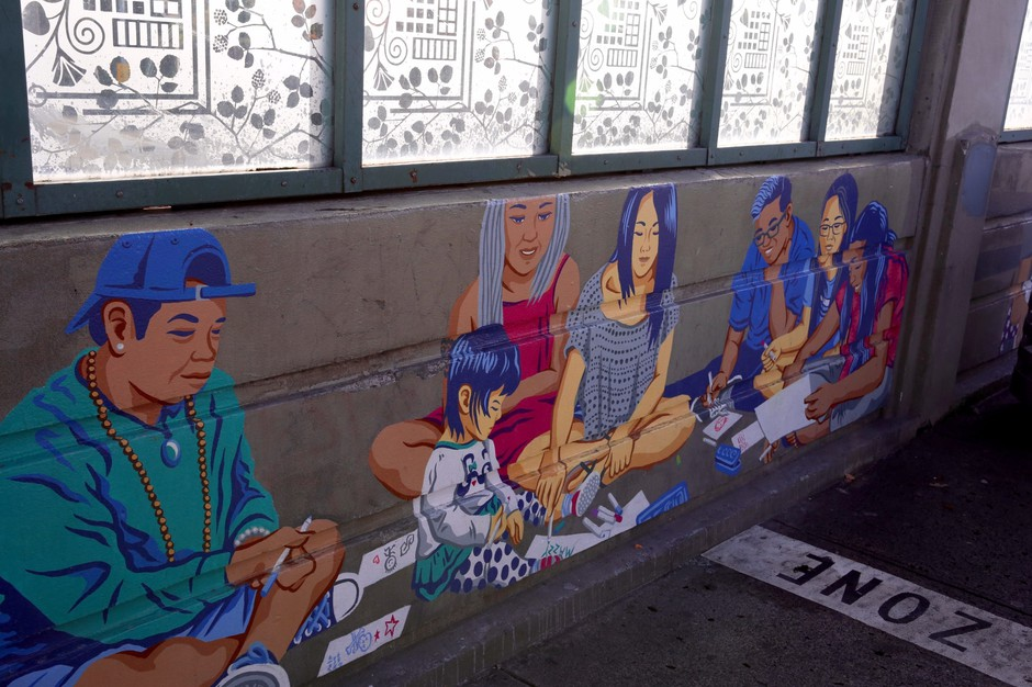A panel on Alex Chiu's mural depicting members of Asian Leaders for the Liberation of Youth, an Asian Pacific American Network of Oregon (APANO) program, teaching Chiu's daughter Mazzy how to write her name.