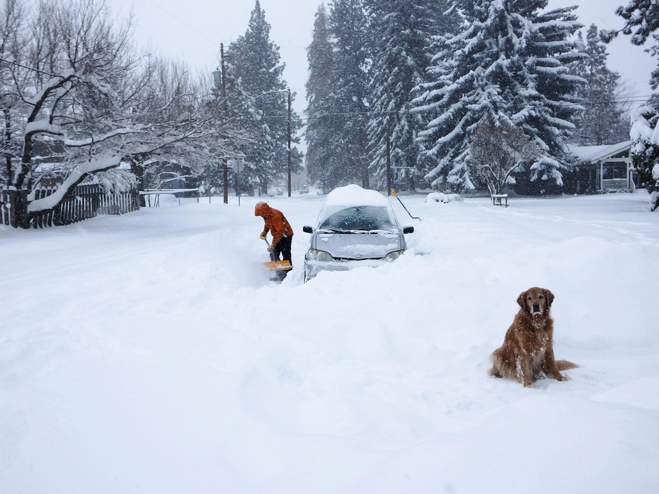 Jason Arbetter of Bend shovels out a spot for a car that got stuck trying to travel down First Street on February 25, 2019.