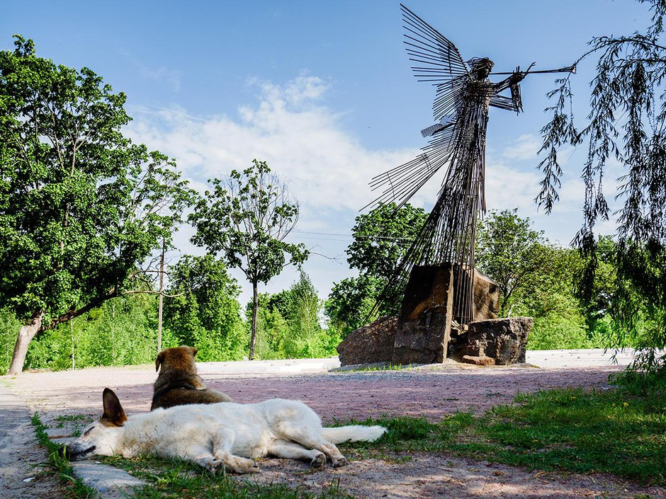 """""""Mia, lounging in front of the trumpeting angel memorial"""", a film still from Julia Oldham's documentary, """"Fallout Dogs"""", shot in the Chernobyl exclusion zone."""