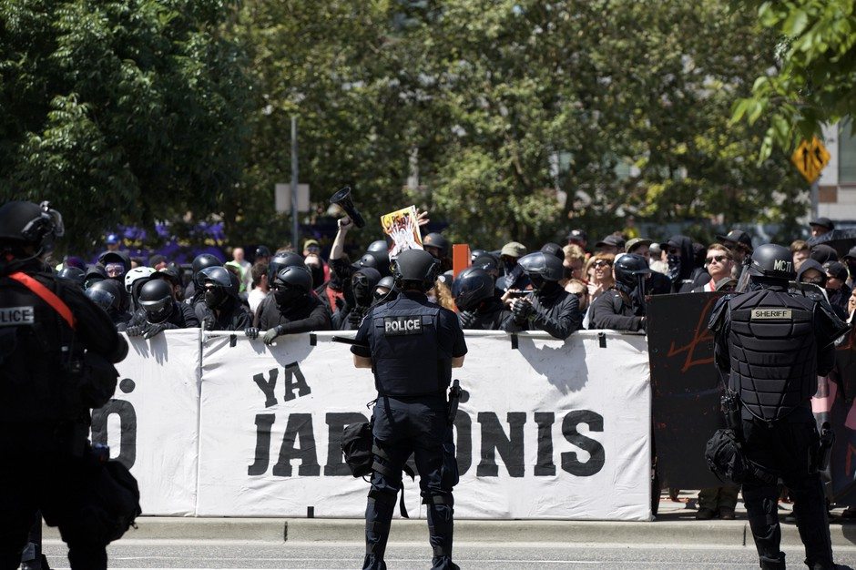 Portland Police in riot gear stand between right-wing protesters and counter-protesters.