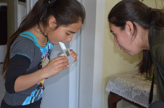 Adriana Perez, with the Yakima Valley Farm Workers' Clinic, administers a breathing test to 10-year-old Azul, who has poorly-controlled asthma.