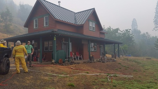 Fire crews install hoses and sprinklers around the McCaleb Ranch building to protect it from the Chetco Bar Fire.