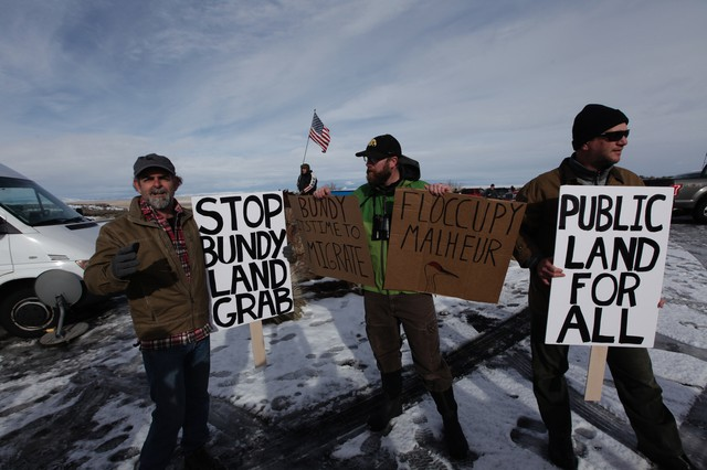 Environmentalists hold signs supporting federal land management at the Malheur National Wildlife Refuge.