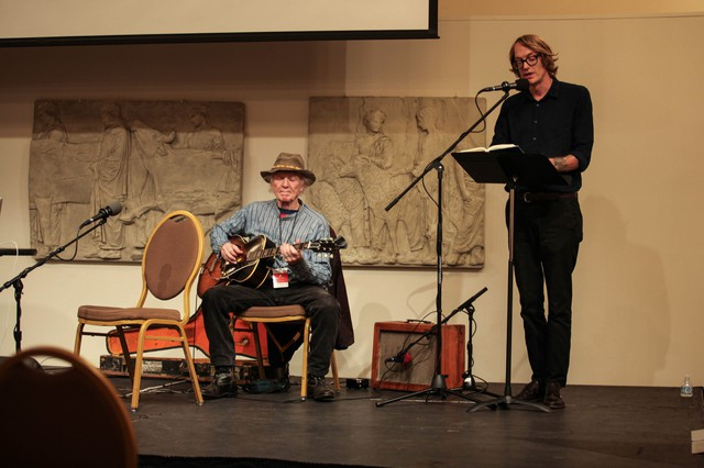 """Author Patrick Dewitt (right) reads a passage from his book """"Undermajordomo Minor,"""" accompanied by Michael Hurley on guitar atWordstock."""